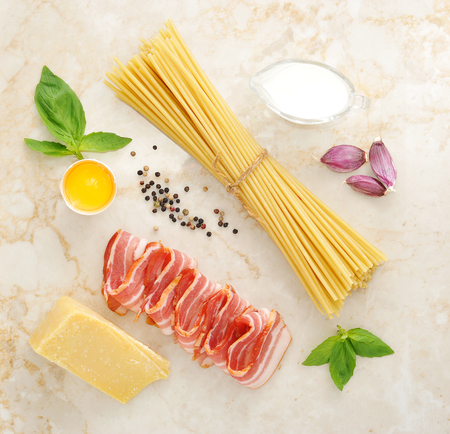 spaghetti bolognese: set of products for pasta Carbonara - spaghetti, bacon, cream, Parmesan cheese, Basil, egg, garlic, spices - on a marble background, top view