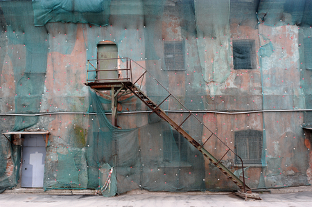 second floor: old stairs to the second floor of a building construction covered by mesh in St. Petersburg, Russia