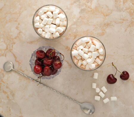 marshmallows: Cocoa with marshmallows and cherry on a marble background. top view Stock Photo