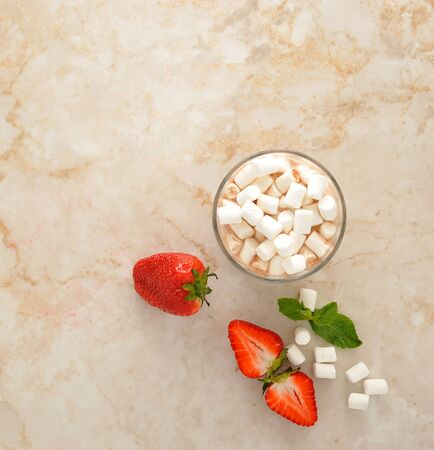 marshmallows: Cocoa with marshmallows and strawberries on a marble background. top view