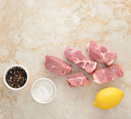 limon: Sliced raw pork meat and salt, limon and pepper on a marble background. Top view Stock Photo