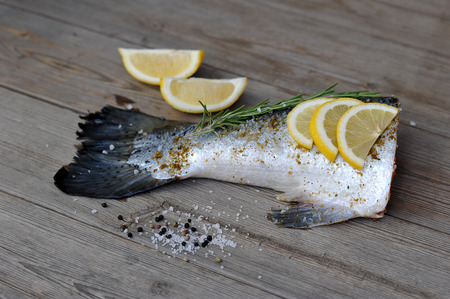 fish tail: raw fish tail salmon with lemon and rosemary on wooden background Stock Photo