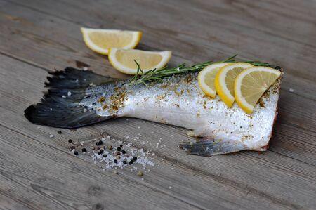 rosemary: fishtail salmon marinated with lemon and rosemary on wooden background Stock Photo