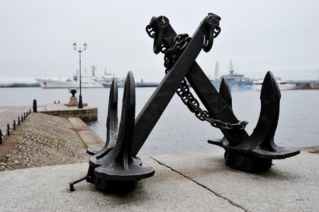 ship anchor: black cast iron anchor at the pier in Kronstadt, Saint Petersburg