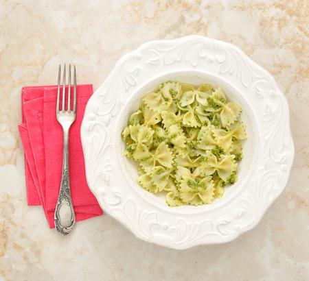 comida: massas curva-se com pesto em uma bacia em um fundo de m Imagens