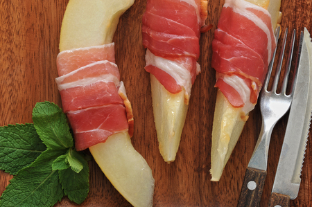slices of melon wrapped in bacon with mint leaves on a wooden platter. selective focus, closeup Stock Photo