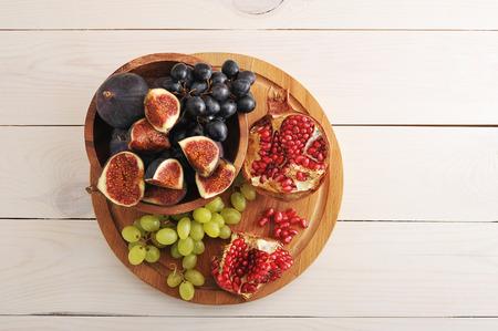 과일 플래터 - 무화과, 포도, 석류 나무 배경 - 상위 뷰