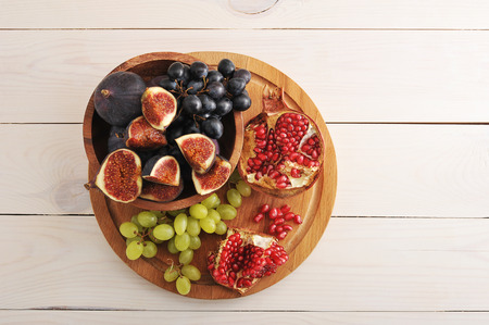 fruitschaal - vijgen, druiven, granaatappel op houten achtergrond - bovenaanzicht