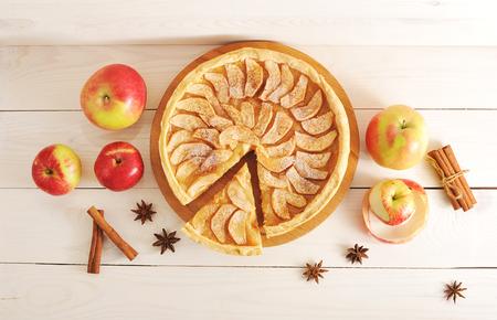 Apple pie tart, ingredients - apples and cinnamon on rustic wooden background - top view