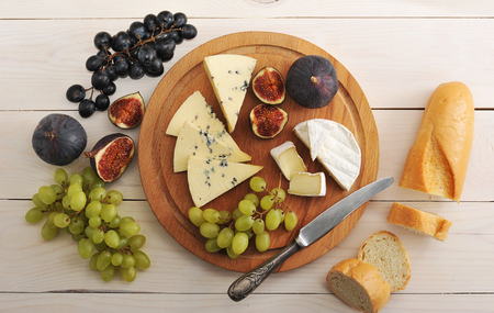 cheeseboard: cheese plate - various types of cheeses and figs and grapes on a white wooden background - top view