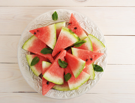 sliced watermelon: watermelon slices on plate on wooden white background - top view Stock Photo