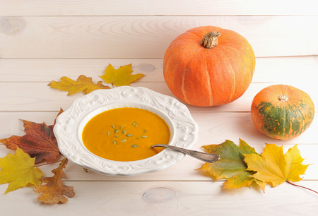 autumn still life of pumpkin soup, maple leaves and oak,  whole pumpkin on white wooden background
