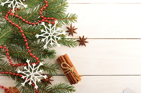 new year and Christmas background with Christmas trees, dried oranges, cinnamon and star anise on wooden background - top view