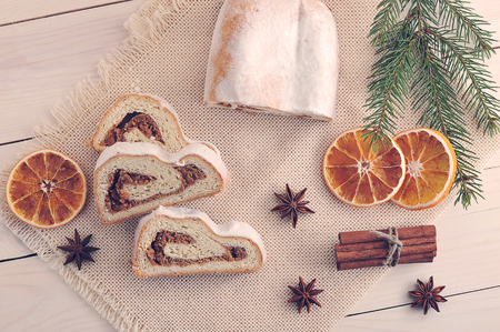 Christmas cake cut into pieces, dried oranges, cinnamon, star anise, spruce twig on wooden background