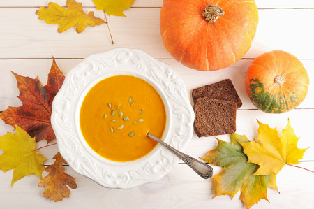 autumn still life of pumpkin soup, maple leaves and oak, bread and a whole pumpkin on white wooden background - top view