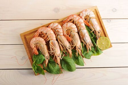 king size: tiger prawns with Basil leaves and slices of lime on wooden background - top view Stock Photo