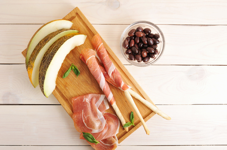 melon slices and bacon on bread sticks with olives on white wooden background - top view Stock Photo