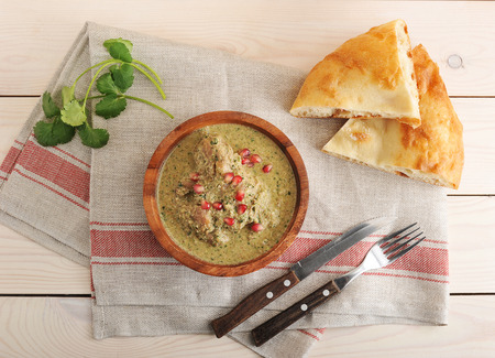 Chakhokhbili – recipe Georgian cuisine - with pita bread and parsley on wooden background