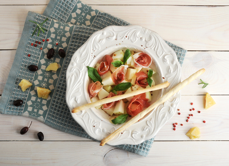gressins: ham with melon and breadsticks on a plate, olives and Parmesan cheese on wooden background - top view Banque d'images