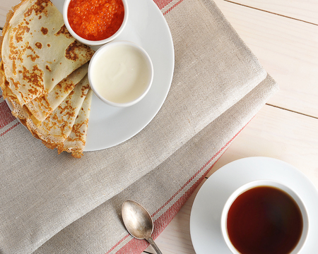 pancakes with caviar and sour cream on a saucer and a mug with tea on wooden background - top view