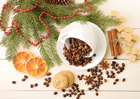 coffee beans poured into a mug at the Christmas backdrop from sugar, tree branches, cinnamon and anise on wooden background - top view Stock Photo