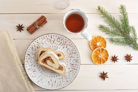Christmas cake with powdered sugar, cut into slices, tea, dried oranges, cinnamon and Christmas tree branch on wooden background top view