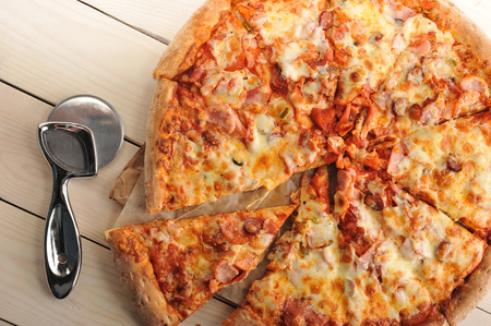 pizza cutter: pizza with cheese and spicy sausage cut into slices and the pizza cutter on wooden background - top view