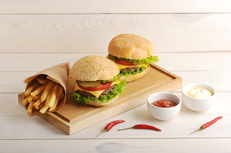 fried potatoes in a paper bag, cheese sauce, ketchup, and two hamburger on wooden background 写真素材