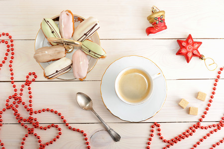 cakes in a dish and coffee with Christmas toys and beads on wooden background - top view