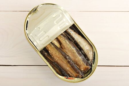 canned sprats in a tin on wooden background - top view Stock Photo
