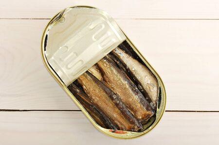 ingeblikte sprotten in een blik op houten achtergrond - bovenaanzicht