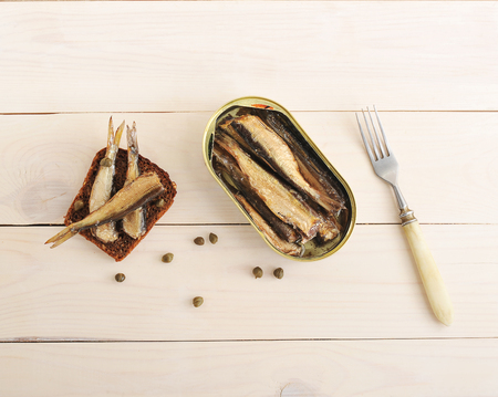 sardine can: sandwich with rye bread, capers and canned sprats in a tin on wooden background - top view