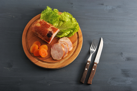 Meatloaf with dried apricots and lettuce on a wooden round Board and a knife and fork on a black wooden rustic background - top view Stock Photo