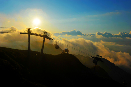 sunset on a background of clouds and the Caucasus mountains, pillars of the ropeway with cabins in the resort of Krasnaya Polyana, Sochi, Russia