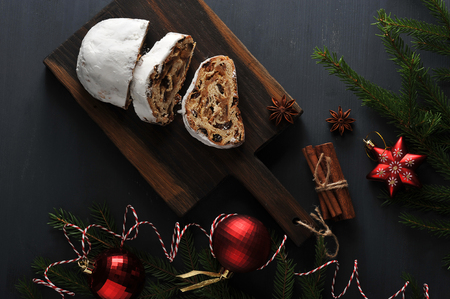 traditional Christmas cake pie with raisins and nuts with tree branches and toys - top view