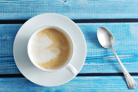 frothy coffee - cappuccino in a white mug on a blue wooden background - top view
