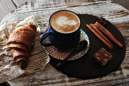 Mattina Colazione al caffè cappuccino in una tazza, cornetto, cannella e cioccolato Archivio Fotografico - 92798324