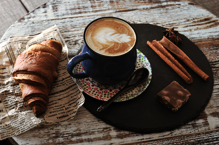 Morning Breakfast at cafe cappuccino in a mug, croissant, cinnamon and chocolate Standard-Bild