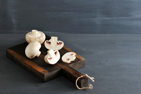 Raw Mushrooms whole and chopped on a wooden rustic background  Stock Photo