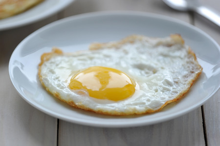 Breakfast one fried egg on a white plate