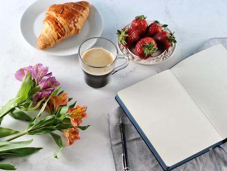 Morning  romantic Breakfast - coffee mag, empty notebook , flowers, croissant, strawberries - cozy summer breakfast, top view, flat lay