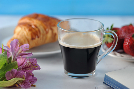 Morning romantic Breakfast - coffee mag, empty notebook , flowers, croissant, strawberries - macro