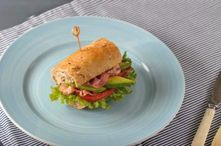 sandwich with bacon and avocado pierced with a skewer - macro Stock Photo