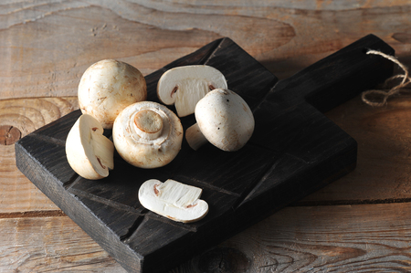 Fresh white mushrooms champignon on rustic board wooden background. Фото со стока