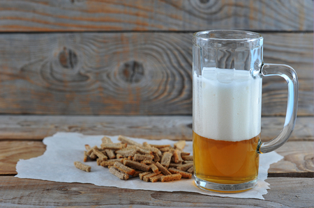glass mug with beer with foam, snack crackers on wooden rustic background