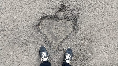 sign of the heart on the asphalt and feet in sneakers - top view Stock Photo - 103060581