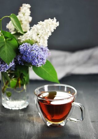 morning black tea in a transparent mug and a bouquet of blooming lilac