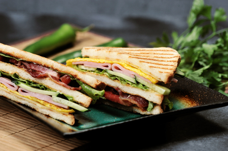 triangular shaped sandwiches with ham and omelet on a plate on a dark rustic background