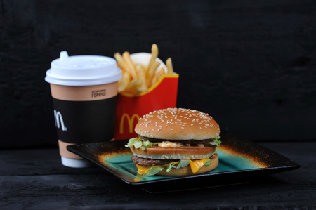 St.Petersburg, Russia - 12 August 2018: McDonald's meal on rutic black background, includes Big Mac, French Fries, Coffee cup
