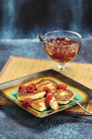cheesecakes or cheese pancake with fresh raspberries and raspberry jam on a bamboo substrate on a blue rustic background